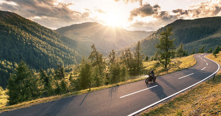 rider on mountain roads at sunrise - solo motorcycle touring